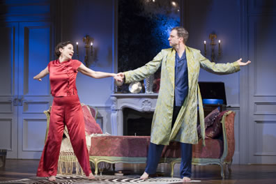 Amanda in red pajamas and Elyot in blue pajamas with green print robe dance with arms outstretched, holding hands, in front of a chez lounge in an apartment with marble mantled fireplace, large mirror, and wall candelabra