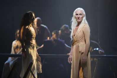 The nameless woman with long white hair and wearing a loose-fitting plain tan dress with young Salome in white pleated skirt and leather corset crosses behind; at a table in the background is a tableaux of men.