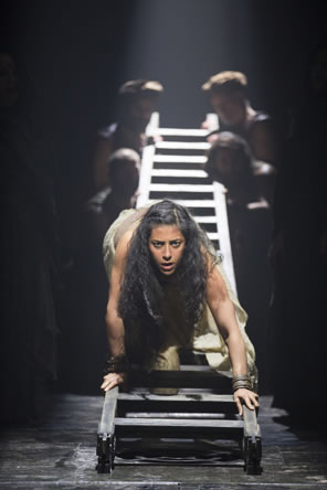 Salome climbs headfirst down a ladder held up by an ensemble of actors at the other end.