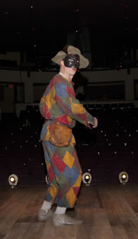"Steven Epp in patchwork costume and mask in ""The Servant of Two Masters"""