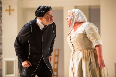 Orgon in a black frock and black wig with curls on the side, hands clenched at his waist, leans in toward Dorine in a simple maids dress and head scarf, shouting back.