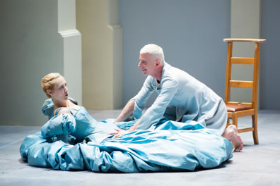 Tartuffe in pale blue smock and on his knees leans over Elmire in a blue ball gown, leaning back on the floor, hands propping her up, and a plain wood chair is behind Tartuffe