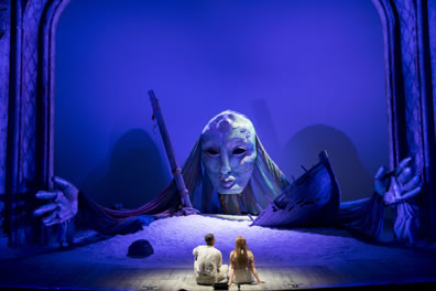 The giant head of Juno is at the back of the stage, with giant hands spread out to the side; the head appearing between the shipwrecked bow and mast on a mound of sand, with the two lovers, backs to us, in the foreground. The whole photo has a blue tone.