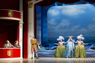 Dangle and Sneer sit in red theater box seats to the left, Puff stands near them talking to them, and to his left in the center of the stage are two women dressed as shorelie (green wide hoops skirts with sillhouettes of towns on the hips and clouds for hats) and a man dressed as an ocean with sun rays for a hat. Behind them is the English channel, a mechanism emulating waves.