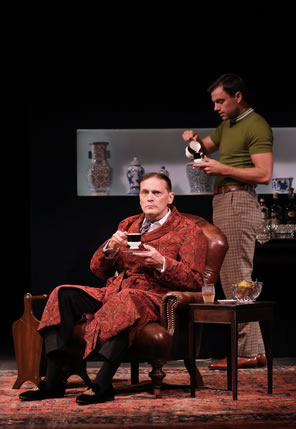 Harry sitting in chair sipping from a tea cup he holds in his right hand over a saucer in his left, he's wearing a rust-patterned robe over a shirt and tie and black pants. Behind him, Bill in tight green pull-over shirt and checkered pants pours tea in his cup; he's standing next to a bar cart with crystal and bottles on top, and a line of Chinese porcelain in a glass case behind him. A Persian rug is on the bloor, and a wood end table and magazine rack are on either side of Harry's chair.