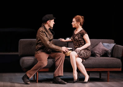 Max in leather jacket, brown pants, and dark brown worker's cap holds a bongo across from Sarah in tight, brown patterned dress, lots of crossed-leg showing, as they sit on the couch.