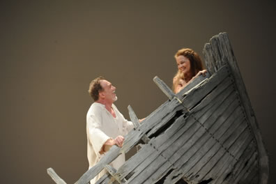 Miranda in the bow of a wrecked boat looks back, smiling, at Prospero behind her in the bow and wearing a ragged white shirt.