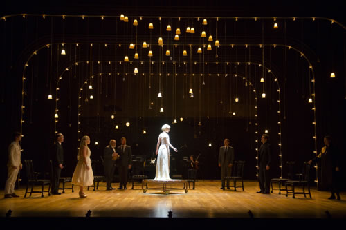 Hermione looking like a statue on a platform on wheels amid layers of lights and lamps hanging down from the ceiling. The rest of the cast stand around the perimeter next to chairs