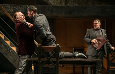 Richard in black shirt and pants kneeling on a table grabs the throat of Hastings standing at one end of the table--he in red dinner jacket and gray leather pants--as Stanley with briefcast and wearing a grey three-piece suit with turtleneck sweater shirt, looks on in consternation. The stairway and wood-paneled wall is int he background.