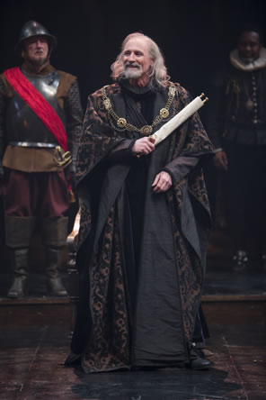 Lear wears black robes with purple pattern, a chain with several medallions draped over his shoulders, and long silver hair to his shoulders, and he carries a scroll in his left hand: a soldier in Renaissance breastplate armor and helmet with knee boots and a red sash stands behind on the left, and on the right is a lord in ruff collar
