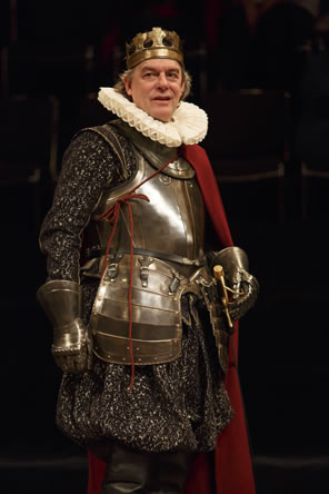 King John in breast plate and hip armor, armored gloves over a black floral cloak, a ruff collar, a red cape, a sword at his hilt, and a simple gold crown