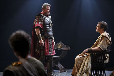 Antony stands in red skirt and cape with leather breastplate and decorative armor hanging down the sleeve and skirt and leather boots facing Octvius in white senator's toga sitting in a wood X-shaped chair with curved arms and legs, The back of somebody's head is in the left of the picture.