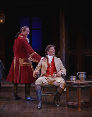 Archer in long red coat with gold embroidery and riding boots, his hair in a pony tail, leans on  the chair in which sits Aimwell, in tan coat and britches, red vest, and fluffy white shirt, black riding boots with brown tops, and long hair. Next to him is a table with pewter ewer and tankards