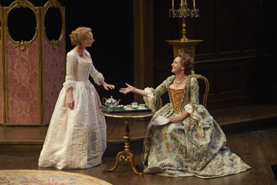 Dorinda is in an all-white floor-length dress, with corset and puffy sleeves, her blond hair done up, and she holds her hand out to the sitting Mrs. Sullen, in a green tapestry dress with gold corset and a neckless. Between them is a teaset on fine table, with, in the background, a calabra on a stand and a pink screen