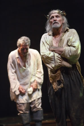 Lear in ragged white shirt and billowing brown pants, weeds stuck in his crown, his arms folded; behind, Gloucester in untucked white shirt and gray pants with knee boots stoops, crying