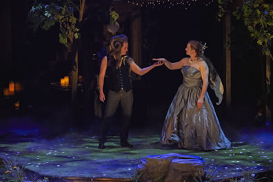 Oberon in black vest and jeans, no shirt, and with rams hors curling over the side of his head holds hands with Titania in silver, strapless ball gown, wings on the back, the stage floor dappled in blue and green lights and reflections of a mirror ball. Trees in the background, large rock in the foreground