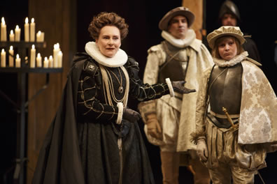 Constance in black dress and cape with silver necklesses, ruff wrists cuffs and collar, and black gloves points to Arthur in armored breast plate, gold patterened cape, ruff collar, pleated baggy pants and gloves and cap, with the Dauphin behind dressed similarly; one of the candalabras is on the left side of the picture.