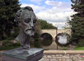 Photo of a bust of Shakespeare with river going under bridge in background