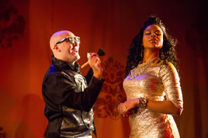 The makeup artist is bald, wearing black leather jacket, and black glasses holding up a brush to Rosalind in a glittering gold, tight dress, jeweled bracelet on her rist, and hair cascading down, her head turned and eyes closed.