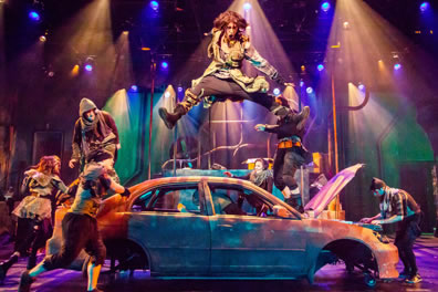 A guy with long hair and patchwork coat leaps, spread legged, high over an abandoned car as other dancers frolic and Amiens plays his keyboard in the opened hood of the car. Pipes are in the background against green and purple wall and multi-color lights.