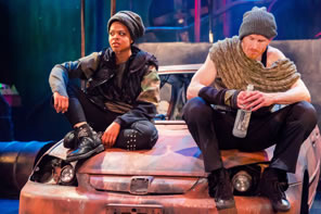 Rosalind in black knit cap, camoflage shirt, black flack vest, and black pants with rivets sits on the hood of the car with Orlando in gray knit cap, shaw, and black pants, holding a bottle of booze.