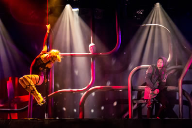 Phoebe to the left has her hands extended along a pole and her legs, with 5-inch platform shoes, tucked up as she dances for Rosalind, wearing a gray hoodie and chained to one of the serpentine pipes at the back of the stage; Jacues mask is sitting at an intersection of two poles in the center of the image.