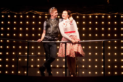 Claudio in leather fest and black jeans, sunglasses pushed up on top of his red head, standing cross legged, has his right hand on the rail and left hand draped around Hero's shoulder; she's wearing a white sweater with embroidered flowers, red polka dot skirt, and red belt; she's looking coyly at Claudio. Background of white lightbulbs