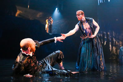 Prospero, in vest and billowing skirt, reaches his hand down to Alonso lying in the water as Miranda and Ferdinand are visible in a spotlight on the cliff at the back of the stage.