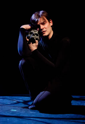 Hamlet all in black blending into black background squats on the foor holding a blackened skull up against his cheek