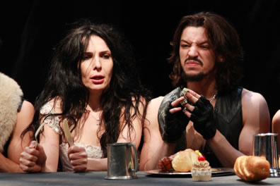 Kate, knife and fork in hand, is denied food by Petruchio, who is eating at a banquet table