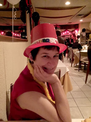 Sarah wearing a red sleeveless blouse, a plastic red party top hat, and a yellow lei with restaurant tables behind her.