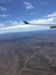 Photo through airline window of desert landscape