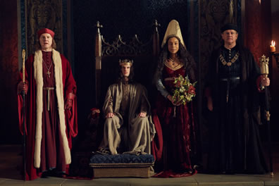Winchester in log red robe with white fur trim, priest hat, scepter stands next to Henry in gold robe and crown sitting on throne, next to Margaret in red dress, gray cloke, white high hat and holding a bouquet of roses standing next to Gloucester in black robes and chain around his neck.