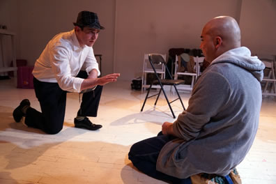 The Duke on one knee with white shirt, black pants and pork pie hat holds a Bible in his left hand and holds his right hand out toward Claudio in gray hoodie and black pants kneeling on the floor