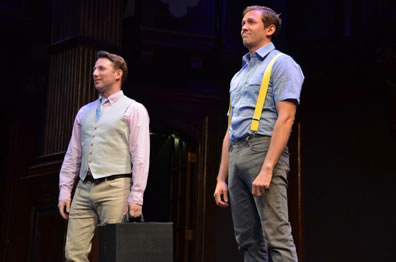 Valentine in pink oxford shirt, blue tie, tan vest and tan jeans holding a black suitcase in his left hand, Proteus in blue work shirt, gray jeans, and yellow suspenders