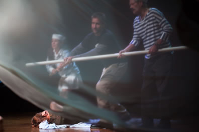A boy in a white sailor outfit, a man in sweatshirts and cargo pants, and a man in striped blue shirt hold a white pole, someone is lying on a sheet on the ground, and a while film flutters over this whole scene in the foreground