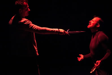 Hamlet stands with his knife pointed at the throat of the King who is kneeling, hands outstretched and laurel wreath in his left hand, his head tilted back as he prays to heaven. Both are cast in a red light on a dark background.
