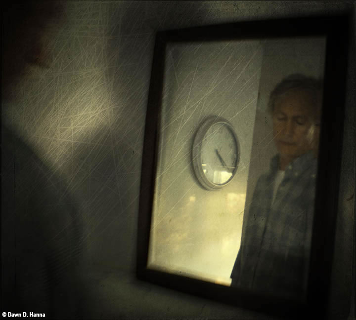 Reflection of a man in checkered work shirt in a mirror, he's looking down, and a clock on the wall is beside him in the reflection: time is 4:20; the shadow of his shoulder is to the left of the image, and the whole has a scratchy veneer