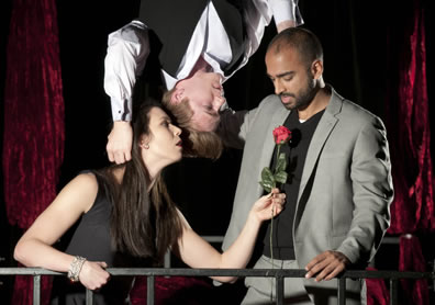 A young woman holds a rose up to a man while another man hanging upside down from above has his hands behind the heads of the other two