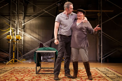 Gore with his arm tight around Packer's neck, she in tunic, dogcap and boots in a space with an oriental rug on the floor, a metal table behind the actors, lights, trash, and scaffolding against the wall