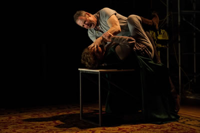 The two lying on the table, Gore on top with hand gripping her face as he screams at her, she fighting back, gripping his arm and kicking her leg up.