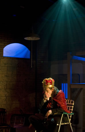 King John wearing a formal red and gold crown, red velvet cape and business suit sits on a green and whit striped lawn chair, leaning forward with hand over mouth, and a single spotlight shines down from the ceiling