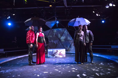 Cornwall in red jacket and black leather pants and Goneril in red dress with black bustier stand under one umbrella; Goneril in purple gray short jacket and blousy pants and Oswald in dark pants and shirt and gray vest stand under the other umbrella.