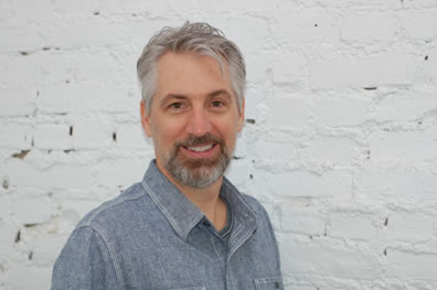 Gray hair, gray-and brown beard and mustach, denim shirt, smiling at the camera in front of a white-painted brick wall
