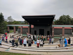 Photo of audience members standing for cast at amphitheater