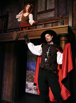 Henriquez on lower stage in cavalier brown lace-up vest, white blouse shirt, black cape with red lining and black wide-brimmed hat holding a rose in his right hand, while up in the balcony Violante holds out her hand coyly; she's dressed in simple olive green tank over white blouse and orange dress