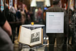"The First Folio, opened to the title page, in a glass case through which we can see a crowd of people in the exhibit, and a descriptive sign on the case titled ""The Title Page."""