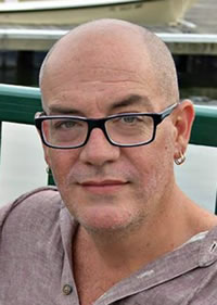 Head shot of Kevin Crawford, bald, wearing glasses, gray shirt