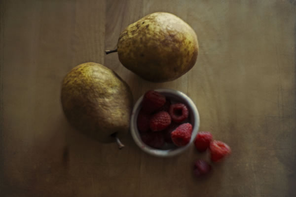Two pears and a bowl of raspberries on a wood counter
