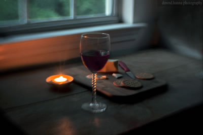 A glass of red wine on a counter next to a candle with a board of crackers and cheese behind